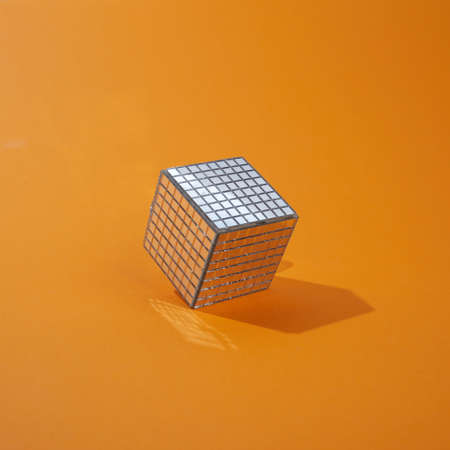 Disco ball cube on orange background. Minimal abstract concept