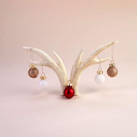 Reindeer horns with christmas balls on biege background. Minimal concept.