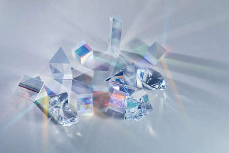 Crystal refracting light in rainbow colors on cold background.
