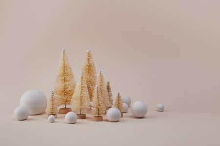 Golden christmas trees with snow ball on biege background. Minimal concept for winter hollydays. Stock Photo