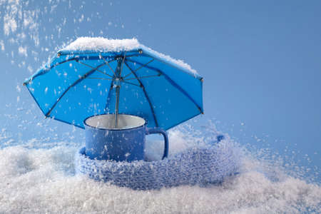 Blue umbrella and cup of coffee on blue background with snow. Blue monday concept.