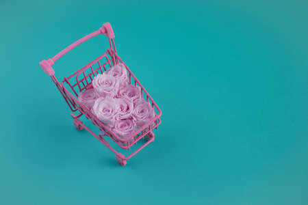 shopping cart full of pink roses on aqua color background. Holiday shopping concept. 免版税图像