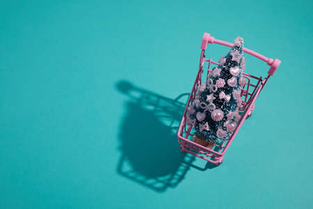 Pink shopping cart with decorated Christmas tree on aqua color background.