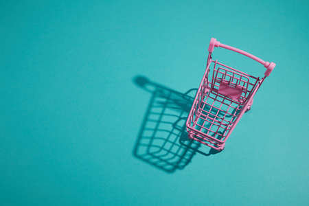 Pink shopping cart trolley on aqua color background.