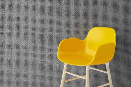 Illuminated yellow chair on a background of grey wall.