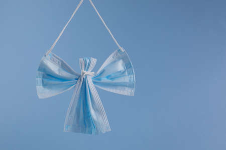 Angel made from face protection mask on blue background. Christmas concept pn pandemic.