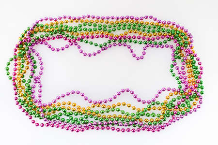 Three colors Mardi gras beads frame on white background 免版税图像