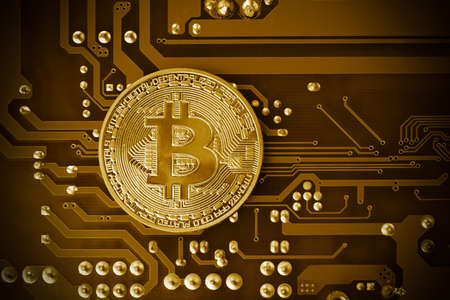 Golden bitcoin on a mainboard. Cryptocurrency concept