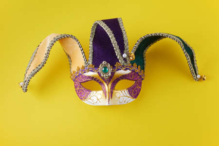 Mardi gras face mask on yellow background with copy space.