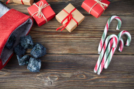 The Befana sock with sweet coal and candy on wooden background. Italian Epiphany day tradition.