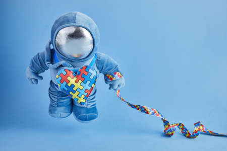 World Autism awareness day background. Blue plush astronaut toy with puzzle heart, autism symbol, on blue background