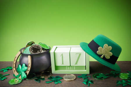 Happy St. Patricks day. Shiny shamrocks, gold coins and leprechaun hat on a wooden background