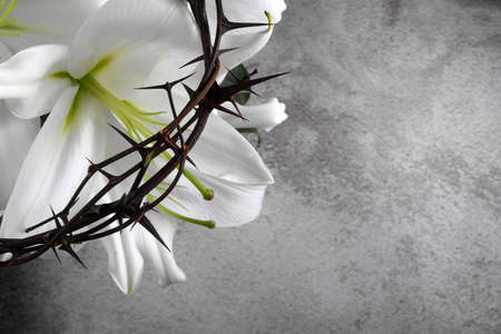 Good Friday, Passion of Jesus Christ. Crown of thorns, nails and white lily on grey background. Christian Easter holiday.