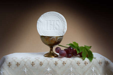The Feast of Corpus Christi Concept. Holy communion and cup of glass with red wine on table.