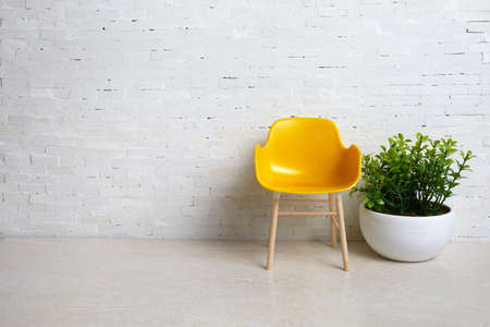 Yellow chair on the background of a white brick wall. Simple interior.