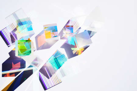 Abstract background with glass geometric figures prisms with light diffraction of spectrum colors and complex reflection.