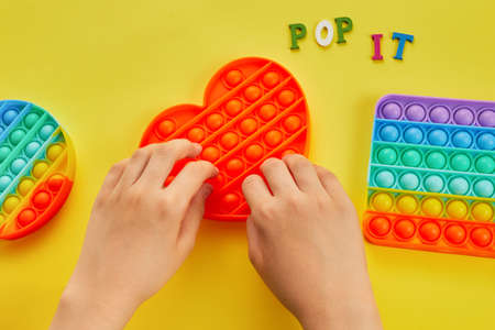 Kid hands playing with colorful pop It fidget toy. Colorful antistress sensory toy fidget push pop it. Stock Photo