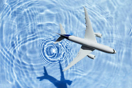 Model plane, airplane on sky blue water background with deep shadow
