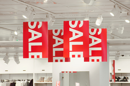 store display: Sale signs in a clothing store hanging from the ceiling