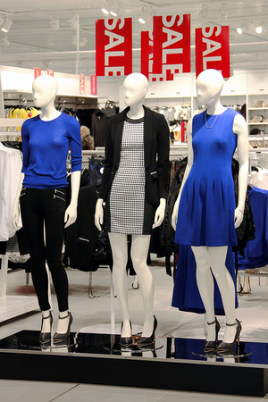 Mannequins displayed in a boutique with a sale signs hanging from the ceiling