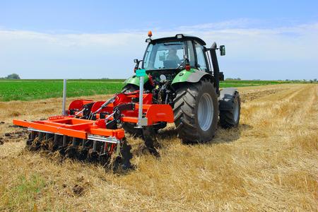 harrow: Tractor with a disc harrow on the farmland Stock Photo
