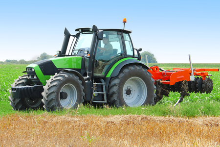 harrow: Tractor with a disc harrow working on the field