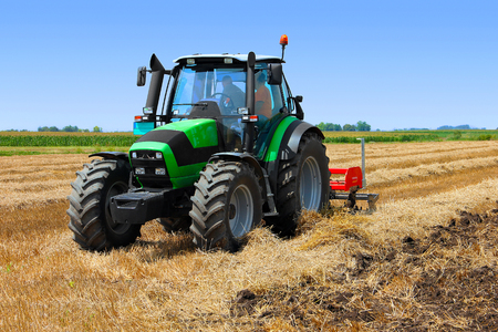 harrow: Tractor working on the field with a disc harrow