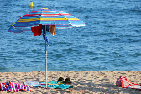 hanged: Umbrella at the sandy beach with wet clothes hanged to dry Stock Photo