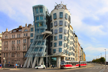 dancing house: PRAGUE, CZECH REPUBLIC, SEPTEMBER 2015. - Famous Dancing House in Prague, with red tram in front