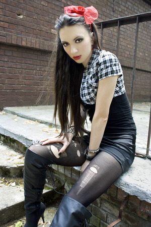 gothic angel: Edgy girl with ripped black leggings and high boots Stock Photo