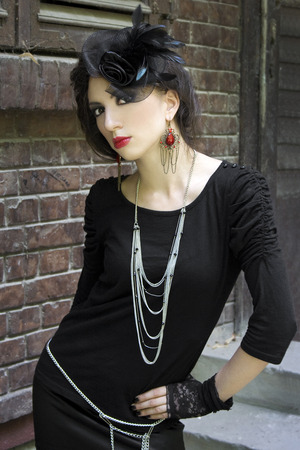 Girl in a gothic inspired look with a hat and elegant hairstyle and jewelry Stock Photo