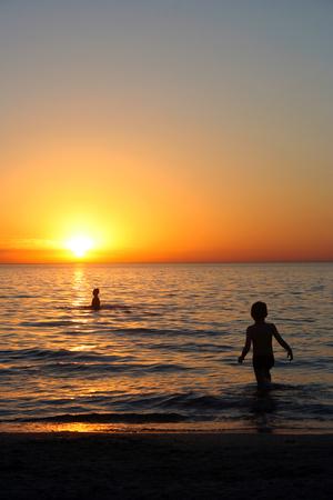 Twee jongens spelen in de zee op zonsondergang Stockfoto
