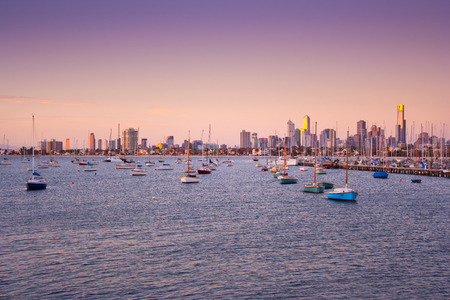 st kilda: Boats at anchor in St. Kilda harbour with Melbourne skyline behind, on sunset. Stock Photo