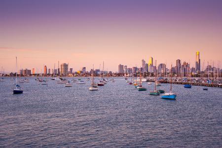 Boten voor anker in St. Kilda haven met Melbourne skyline achter, op zonsondergang.