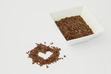 Lijnzaad in een keramische container die op een witte achtergrond. Lijnzaad in de vorm van een hart. Stockfoto