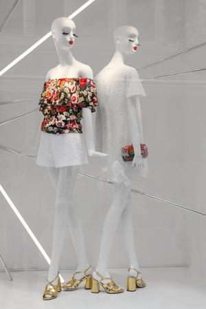 Twee witte mannequins staan in een moderne etalage