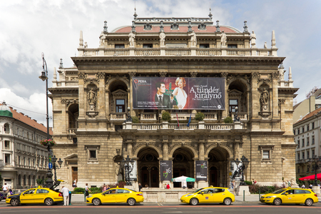JUNE, 2016, BUDAPEST, HUNGARY - Budapest Opera House on Andrassy Avenue with yellow taxi cars in front