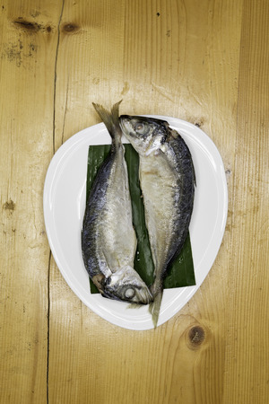 coldblooded: steam with mackerel in white dish on wood table Stock Photo