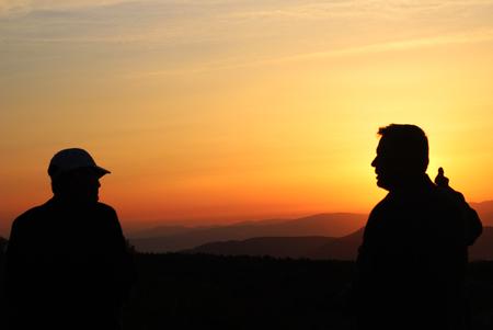 two men talking at sunset