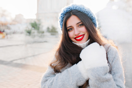 Portrait fashionable young woman walking in sunny city centre. Amazing smiling girl ,red lipstick, blue hat, woolen sweater, having fun outdoor. She looks excited to camera. Place for text Stock Photo
