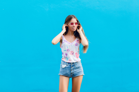 2977de83a7 Horizontal portrait of cute stylish girl on blue background stands and  listens to music on earphones