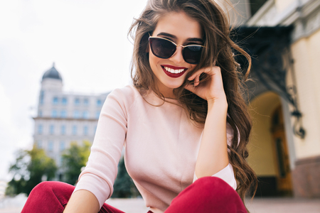 Buttom view of attractive girl in sunglasses with snow-white smile, long hairstyle and vinous lips chilling in city.