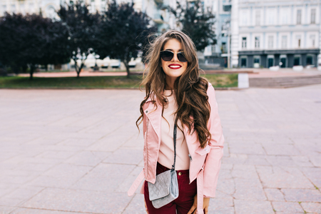 Pretty girl with long hairstyle in sunglasses is walking in city. She wears vinous pants, pink jacket, smiling to camera.