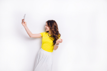 Cute brunette girl listening to music on earphones on smartphone is having fun and takes a selfie. Stock Photo