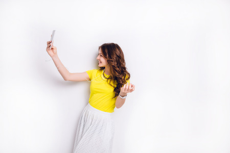Cute brunette girl listening to music on earphones on smartphone is having fun and takes a selfie. She smiles widely. She has long wavy brunette hair. She wears yellow t-shirt and white skirt.
