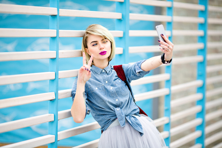 Portrait of a standing girl with short blond hair, bright pink lips and nude make up making a selfie on a smartphone leaning on blue and white stripes fence on the background.