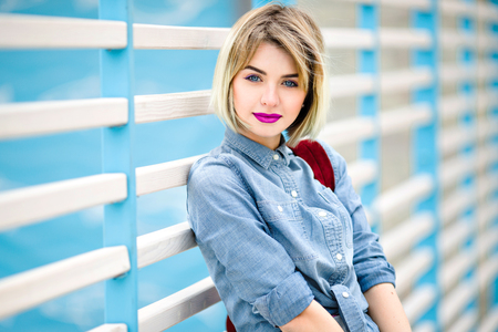 Close portrait of a smiling girl with short blond hair, bright pink lips and nude make up leaning on blue and white stripes fence on the background and wearing blue denim shirt 스톡 콘텐츠