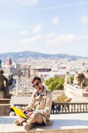 Vertical view of positive guy in beige coat with beard sitting on hight on city background. He is working on yellow laptop, smiling to camera. Stock Photo