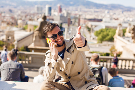 Portrait of positive guy in sunglasses sitting on hight on city background. He wears beige coat,  speaking on phone, smiling to camera.