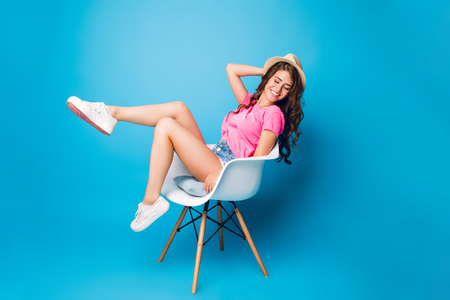 Pretty girl with long curly hair in hat is chilling in chair on blue background in studio. She wears shorts, pink T-shirt, white sneakers. She looks happy.